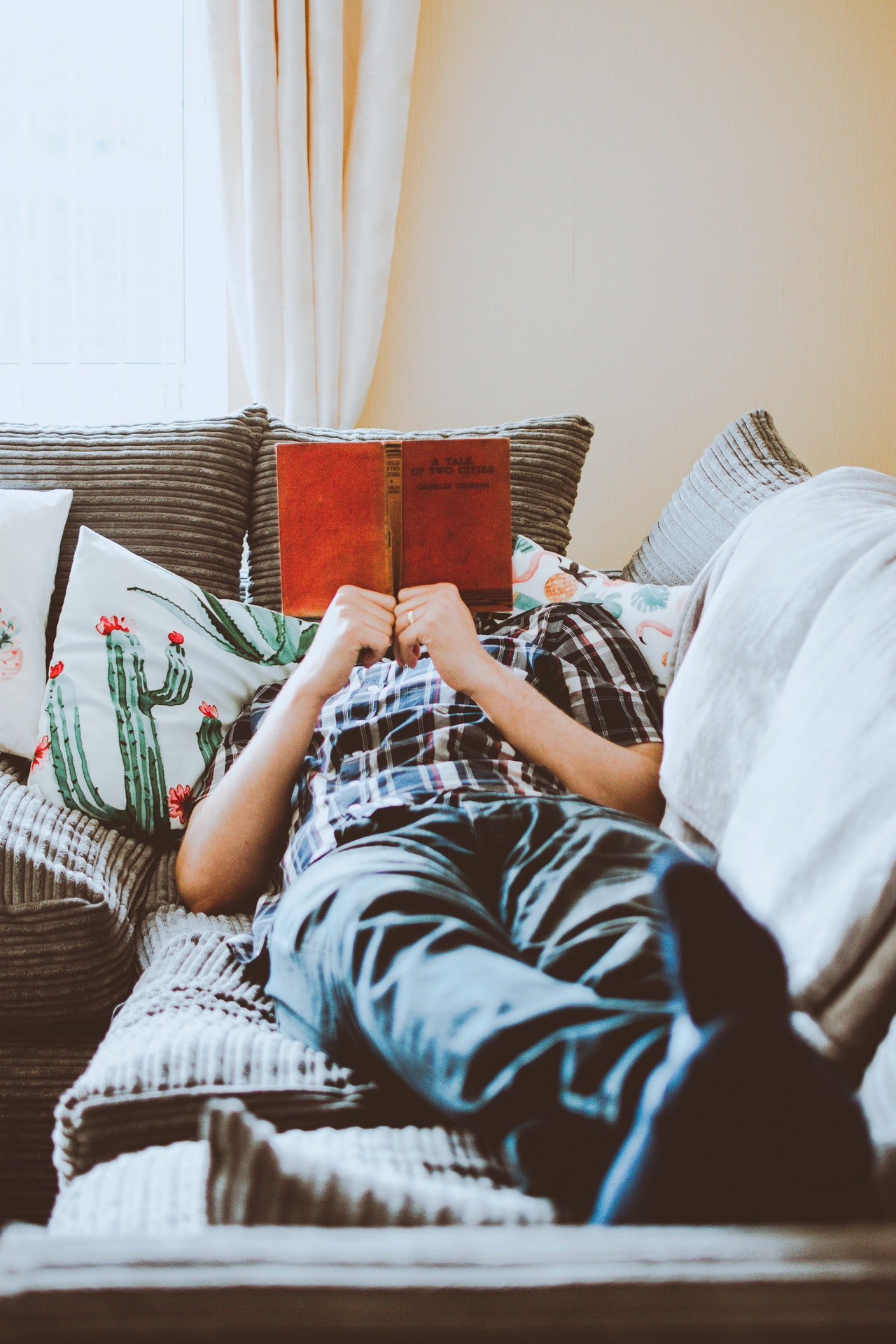 man lounging on the sofa with a book